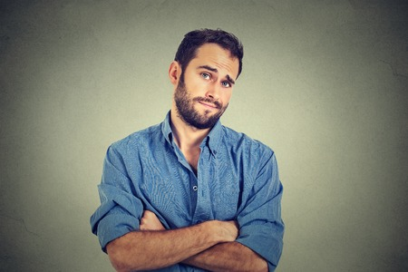 Closeup portrait of skeptical man looking suspicious, some disgust on his face mixed with disapproval isolated on gray  background. Negative human emotions, facial expressions, feelings Stockfoto