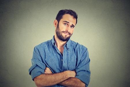 Close-up portret van sceptische man die verdacht kijkt, sommige walging op zijn gezicht gemengd met afkeuring die op grijze achtergrond. Negatieve menselijke emoties, gelaatsuitdrukkingen, gevoelens