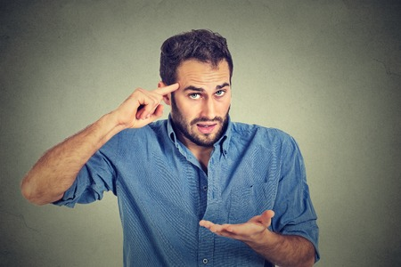 insulted: Closeup portrait of angry mad young man gesturing with his finger against temple asking are you crazy? Isolated on gray wall background. Negative emotions facial expression feeling body language