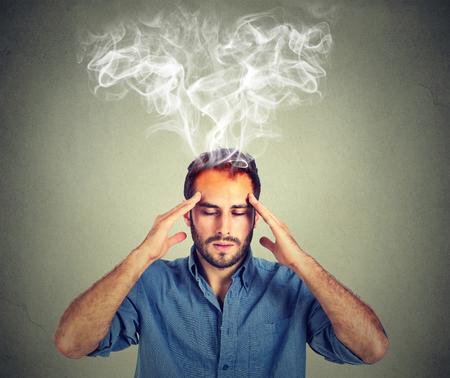 dolor de cabeza: El hombre piensa muy intensamente haber dolor de cabeza aislado sobre fondo gris de la pared Foto de archivo
