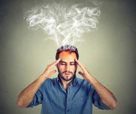 headache pain: man thinks very intensely having headache isolated on gray wall background