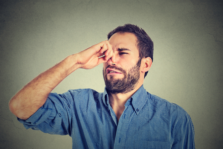 oler: retrato de hombre disgustado pellizca la nariz con los dedos de las manos se ve con algo disgusto apesta situación olor mal aisladas sobre fondo gris de la pared. Expresión de la cara humana de reacción lenguaje corporal