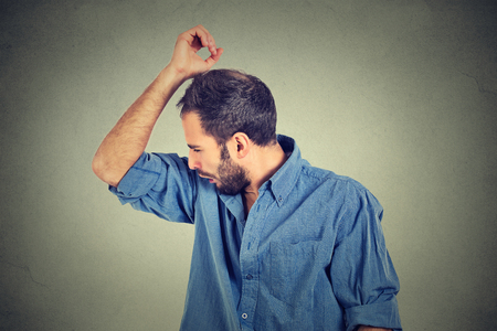 olfato: Closeup portrait of young man, smelling, sniffing his armpit, something stinks, very bad, foul odor situation, isolated on gray wall background. Negative emotion, facial expression, feeling