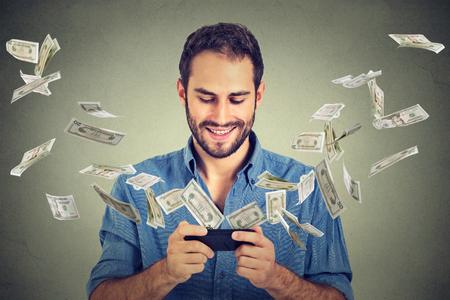 Technologie online bankieren geld overmaken, e-commerce concept. Gelukkig jonge man met behulp van smartphone met dollarbiljetten vliegen weg van het scherm op een grijze muur kantoor achtergrond. Stockfoto