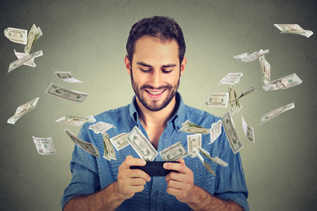 technology transaction: Technology online banking money transfer, e-commerce concept. Happy young man using smartphone with dollar bills flying away from screen isolated on gray wall office background. Stock Photo