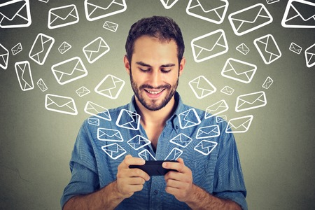 Portrait young happy man busy sending messages emails from smart phone email icons coming out flying of mobile phone isolated on gray wall background. Telecommunications, internet, data plan concept