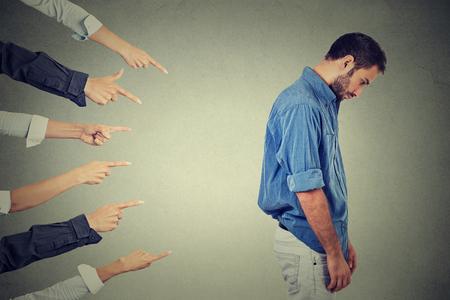 Concept van beschuldiging schuldige man. Zijprofiel triest boos man naar beneden vele vingers wijzen op zijn rug geïsoleerd grijze office muur achtergrond. Negatieve menselijk gezicht meningsuiting emotie gevoel