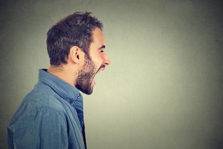 enojo: Lado retrato del perfil de hombre joven enojado gritando