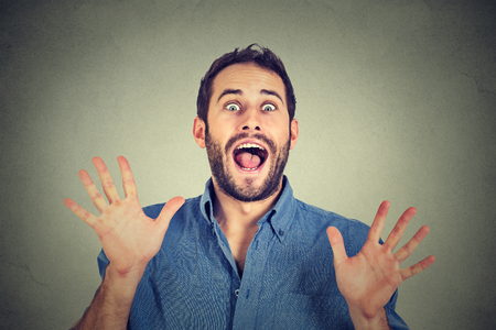 going crazy: Happy young man going crazy screaming super excited isolated on gray wall background