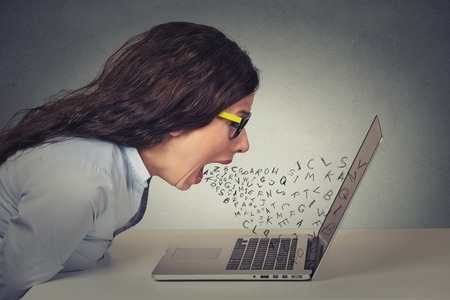 Angry furious businesswoman working on computer, screaming with alphabet letter coming out of open mouth. Negative human emotions, facial expressions, feelings, anger management issues concept Banque d'images