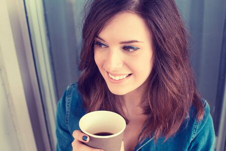 autumn young: Smiling woman drinking coffee outdoors holding paper cup