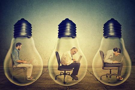 bombillas: Secundarios empleados de la compañía el perfil que se sientan en fila en el interior de la lámpara eléctrica utilizando trabaja en el ordenador en la oficina corporativa aislaron el fondo gris de la pared. Generar el concepto de idea. Las condiciones de trabajo de la productividad