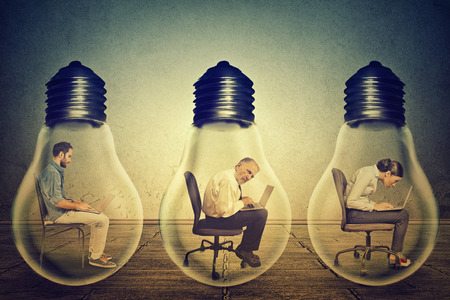lightbulb: Side profile company employees sitting in row inside electric lamp using working on computer in corporate office isolated gray wall background. Generate idea concept. Working conditions productivity