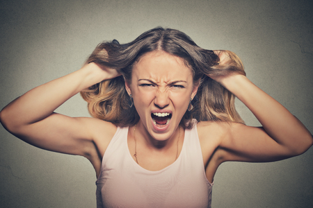 facial expression: Closeup portrait stressed, frustrated angry woman pulling hair out yelling screaming temper tantrum isolated on grey wall background. Negative human emotion facial expression reaction attitude