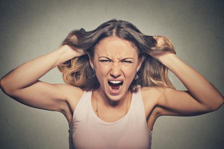 attitude: Retrato de detalle estresado, enojado mujer frustrado tirando de los pelos gritando gritando rabieta aislado sobre fondo gris de la pared. Emoción humana actitud reacción expresión facial Negativo