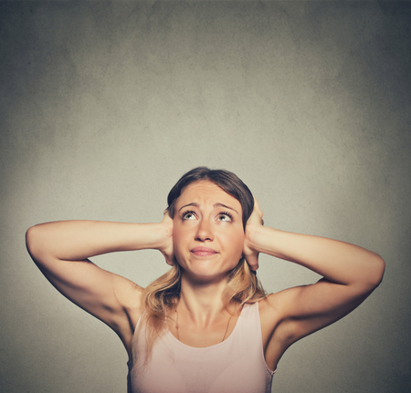 loud music: angry unhappy stressed woman covering her ears looking up stop making loud noise its giving me headache isolated on grey wall background. Negative emotion face expression feeling Stock Photo