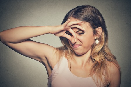 Close-up portret headshot vrouw wringt neus met vingers handen kijkt met afschuw iets stinkt slechte geur situatie die op grijze muur achtergrond. Menselijk gezicht meningsuiting lichaamstaal reactie
