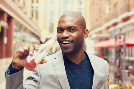 carbonated: Headshot portrait of young smiling man drinking soda from glass bottle isolated on outside outdoors urban street background.