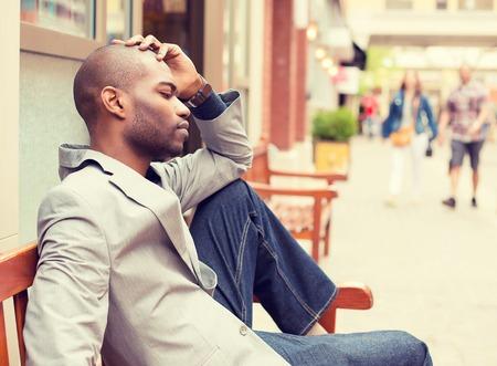 divorcio: perfil lateral destacó joven empresario informal sentado fuera de la oficina corporativa sosteniendo la cabeza con las manos mirando hacia abajo. Negativos emoción humana sentimientos expresión facial.