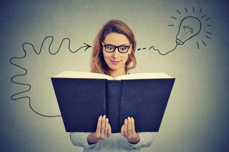 mente: Mujer en los vidrios que lee el libro grande viene con una idea Foto de archivo