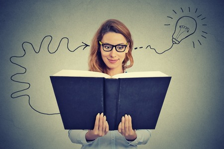 Woman in glasses reading big book comes up with an idea Фото со стока