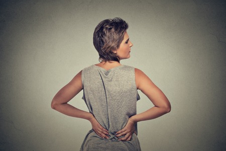 kidney stone: young woman standing with backache back pain isolated on gray background