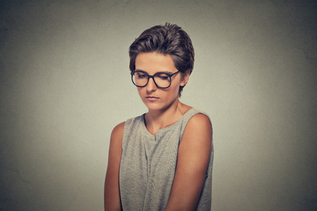 awkward: Lack of confidence. Shy young woman in glasses feels awkward isolated on grey wall background. Human emotion body language life perception Stock Photo