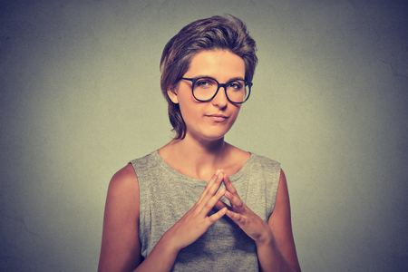 insidious: Closeup portrait of sneaky, sly, scheming young woman in glasses trying to plot something, screw someone isolated on gray background. Negative human emotions, facial expressions, feelings, attitude Stock Photo
