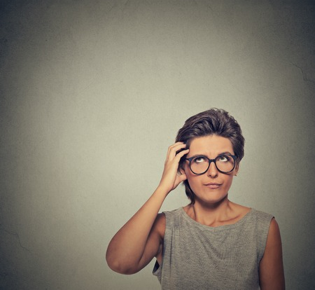 seeks: Confused thinking woman in glasses bewildered scratching her head seeks a solution isolated on gray wall background. Young woman looking up