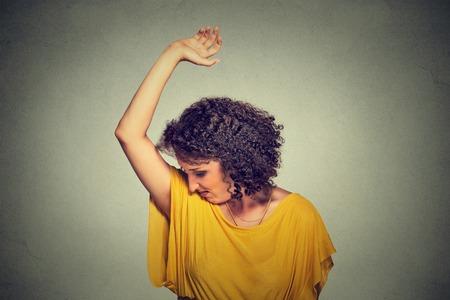 pieds sales: Closeup portrait jeune femme, sentir, renifler son aisselle humide, quelque chose pue, très mauvaise situation de mauvaise odeur isolé gris mur arrière-plan. Émotion humaine expression faciale sentiment réaction négative Banque d'images