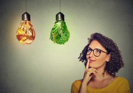 people human mind: Portrait beautiful woman thinking looking up at junk food and green vegetables shaped as light bulb isolated on gray background. Diet choice right nutrition healthy lifestyle wellness concept Stock Photo