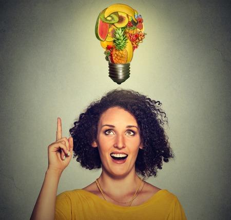comiendo frutas: Comer idea y consejos de dieta saludable concepto. La mujer del primer tiro en la cabeza vertical mirando hacia arriba bombilla hecha de frutas sobre la cabeza aisladas sobre fondo gris de la pared. Foto de archivo