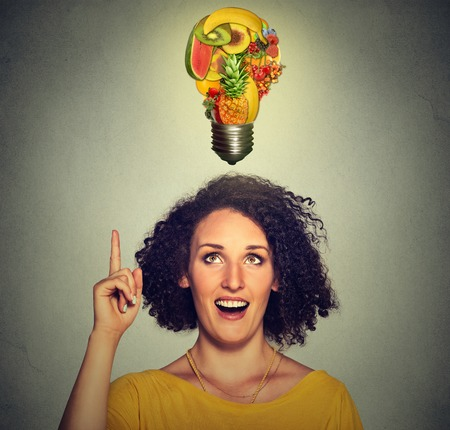 dietitian: Eating healthy idea and diet tips concept. Closeup portrait headshot woman looking up light bulb made of fruits above head isolated on gray wall background.