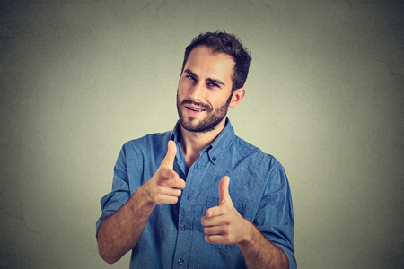 Portrait handsome young smiling man giving thumbs up pointing fingers at camera, picking you as friend isolated on grey wall background. Positive human emotion facial expression sign body language Standard-Bild