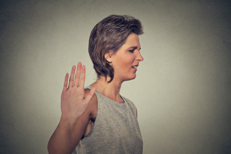 stressed business woman: Closeup portrait young annoyed angry woman with bad attitude giving talk to hand gesture with palm outward isolated grey wall background. Negative human emotion face expression feeling body language