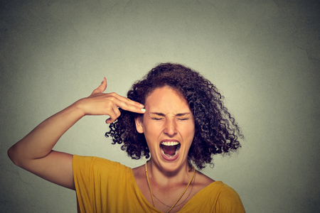 difficult lives: Headshot portrait young woman committing suicide with finger gun gesture isolated on grey wall background. Human emotions face expressions. Overworked overwhelmed young woman. Too many things to do Stock Photo