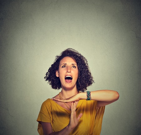 stop time: Young woman showing time out hand gesture, frustrated screaming to stop isolated on grey wall background. Too many things to do. Human emotions face expression reaction