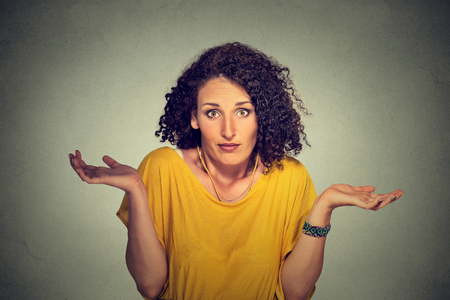 disregard: Portrait dumb looking woman arms out shrugs shoulders who cares so what I dont know isolated on gray wall background. Negative human emotion, facial expression body language life perception attitude Stock Photo