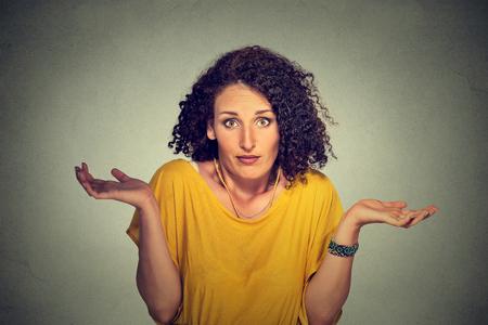 Portrait dumm aussehende Frau die Arme aus zuckt die Schultern, die kümmert sich so, was ich weiß nicht auf graue Wand Hintergrund. Negative menschliche Emotionen, Mimik Körpersprache Leben Wahrnehmung Haltung