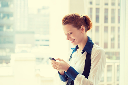 texting: Side profile portrait beautiful young business woman texting on her smart phone isolated on acuity urban background Stock Photo