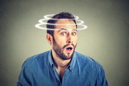 disbelief: Head is spinning. Surprise astonished man. Closeup portrait man looking surprised in full disbelief wide open mouth isolated on grey wall background. Human emotion face expression body language.