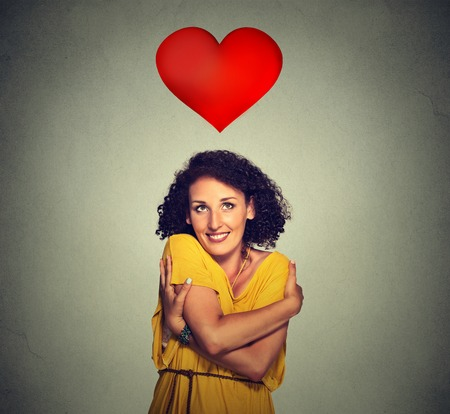 Closeup portrait smiling woman holding hugging herself with red heart above head isolated gray wall background. Positive human emotion, facial expression feeling, attitude. Love yourself concept