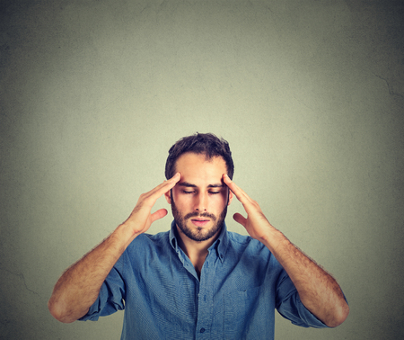 man thinking very intensely concentrating isolated on gray wall background Stockfoto