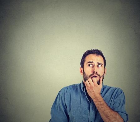 Close-up portret nerveuze benadrukt jonge man student bijten nagels te kijken angstig verlangen iets geïsoleerd op een grijze muur achtergrond. Menselijke emotie gezicht gevoel