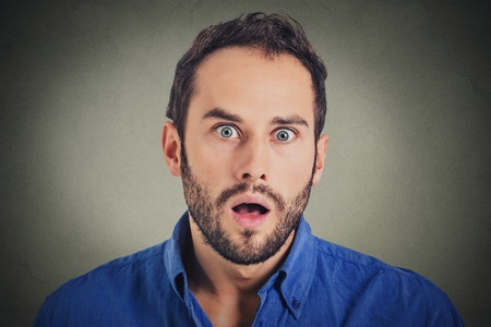 portrait man: Surprise astonished man. Closeup portrait man looking surprised in full disbelief wide open mouth isolated on grey wall background. Positive human emotion facial expression body language. Funny guy Stock Photo