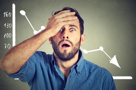 Gefrustreerd benadrukt geschokt zakelijke man met de financiële markten grafiek grafisch naar beneden op grijs kantoor muur achtergrond. Slechte economie concept. Uitdrukking van het gezicht, emotie, reactie