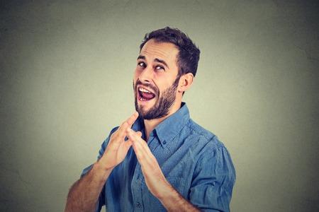 防衛: クローズ アップの肖像画怒って怒って、空手チョップで空からの攻撃で手を上げる fuus 男分離灰色の壁背景。負の感情表情感身体言語、サインとシ