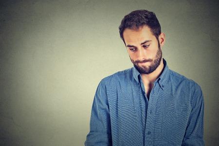 Mangel an Vertrauen. Shy junger stattlicher Mann fühlt sich peinlich isoliert auf grauen Wand Hintergrund. Menschliche Emotionen Körpersprache Leben Wahrnehmung Standard-Bild