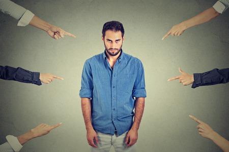 persona deprimida: Concepto de acusación hombre culpable. Hombre triste disgustado deprimido mirando hacia abajo muchos dedos apuntando hacia él aislados fondo gris pared de la oficina. Negativo rostro humano emoción expresión sentimiento Foto de archivo
