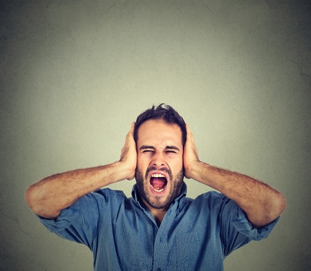 hands on head: Portrait young man screaming mouth open, holding head with hands, wearing casual blue shirt, isolated on gray wall background. Human face expression emotion
